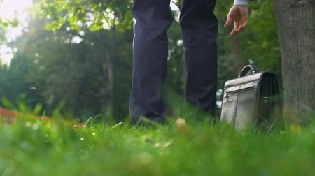 aktetas : Man in suit leaving his case on grass and happily running into forest.
