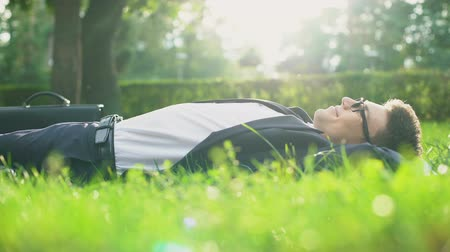 レクリエーション : Happy man in suit lying on grass and enjoying sunny day, harmony with nature
