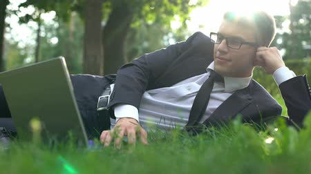 maletin : Businessman lying on grass in park and working on laptop, harmony with nature Archivo de Video