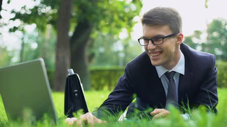 optimista : Successful young manager lying on green grass, smiling and chatting on laptop Stock mozgókép
