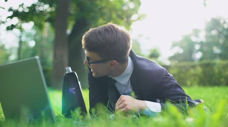 optimistický : Happy businessman lying on grass and relaxing after hardworking, inner harmony