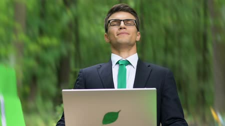 breathing fresh air : Healthy employee taking deep breath while working on laptop in park. Stock Footage