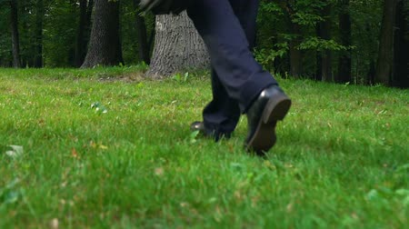 pozitivní : Male in business suit putting down briefcase on grass walking away, freedom