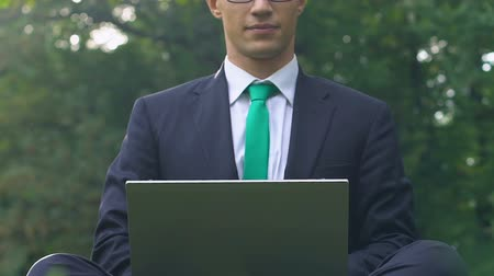 breathing fresh air : Young male in suit sitting on grass typing on laptop, freelance employment
