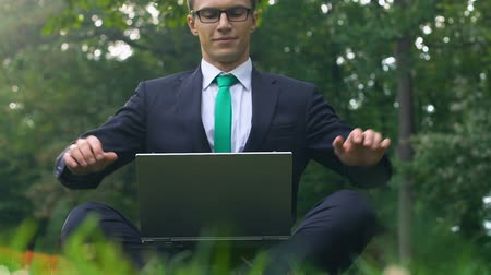 breathing fresh air : Office worker sitting on grass in park with laptop breathing deep and stretching Stock Footage