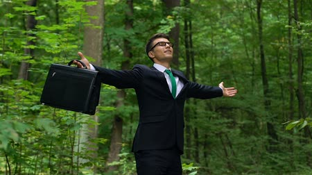 yatıştırıcı : Young man in business suit breathing deep outdoors, abstracting from city stress