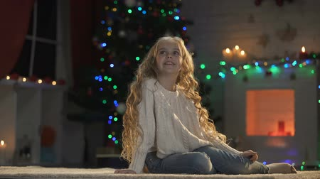 miraculous : Girl sitting on floor in room decorated for X-mas, waiting Santa, holiday magic