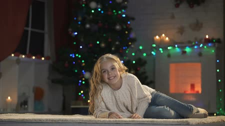 happy socks : Nice girl lying on floor under glowing X-mas decorations, smiling and having fun Stock Footage