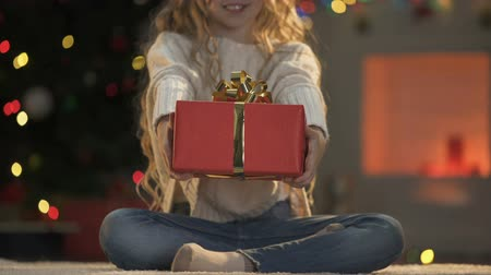 kinderwens : Little girl holding out X-mas present to camera, holiday decorations sparkling