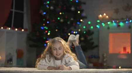 christmas tree with lights : Little girl writing letter to Santa lying on floor, belief in magic fairy-tale
