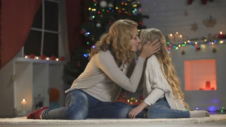 anne : Beautiful lady kissing and hugging daughter, waiting Christmas eve celebration Stok Video