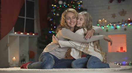 happy socks : Adorable girl hugging mother under sparkling Christmas tree, winter holidays