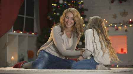 fireside : Mom and daughter having fun, tickling each other near Christmas tree, holidays