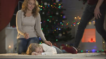 coming home : Adorable girl fallen asleep under X-mas tree, happy parents coming and stroking