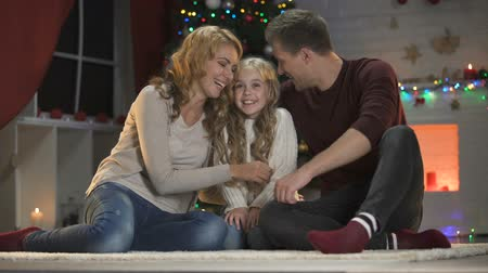 comfortable : Cute little girl telling happy parents X-mas wish, they hugging her and smiling