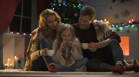 miraculous : Happy family drinking hot cocoa near sparkling Christmas tree, miraculous day