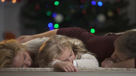 coming home : Family fallen asleep under Christmas tree waiting Santa Claus, belief in magic
