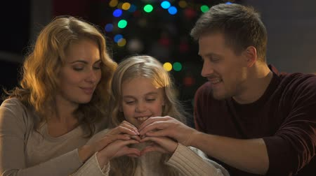 miraculous : Happy family making heart of hands and hugging, Christmas decorations sparkling