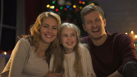 keresik : Young family hugging, laughing and looking to camera, Christmas lights sparkling
