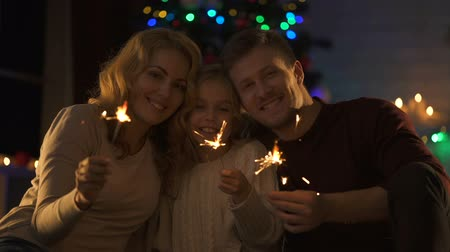 csőd : Cheerful family with Bengal lights looking to camera, enjoying magic Christmas