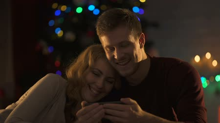 meghittség : Nice couple watching movie on smartphone under sparkling X-mas tree, intimacy Stock mozgókép