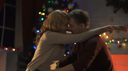 intimiteit : Awesome tender couple hugging near sparkling Christmas tree, celebrating holiday
