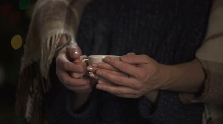 meghittség : Man hands tenderly cupping lady holding coffee, lights glowing on background