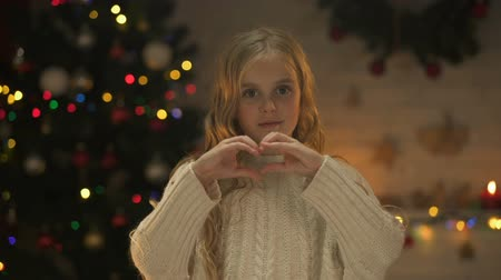 csőd : Cute girl making heart with hands looking to camera, X-mas tree glowing behind