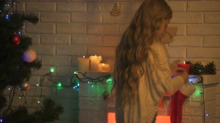 christmas dekorasyon : Long-haired blond girl hanging sock on fireplace waiting Santa Christmas miracle Stok Video