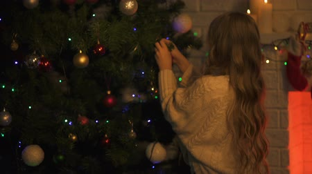 happy socks : Cute girl decorating Christmas tree preparing for holiday eve, family traditions Stock Footage