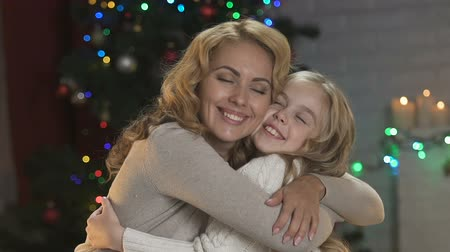 csőd : Adorable mother and daughter hugging on background of illuminated Christmas tree Stock mozgókép
