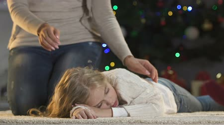 coming home : Caring parents stroking little daughter sleeping near X-mas tree cant wait gifts