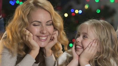 miraculous : Cheerful mother and daughter having fun, nuzzling near Christmas tree, holidays