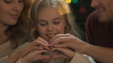 x mas : Friendly family making heart with hands, love and care, Christmas celebration