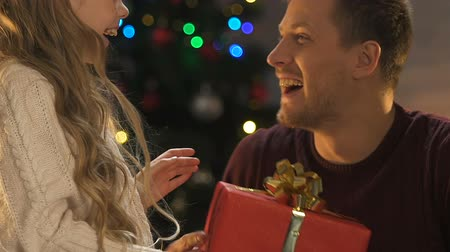 christmas tree with lights : Little daughter presenting x-mas gift to father, cute girl hugging loving dad Stock Footage