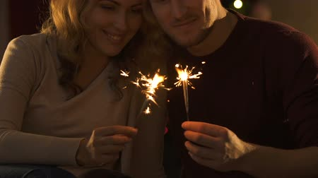 newyear : Couple in love holding bengal lights and kissing, celebrating New Year Eve Stock Footage