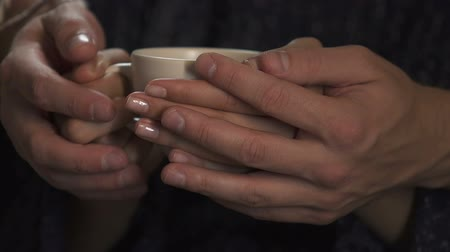 okşayarak : Male and female hands holding cup of hot coffee together, caring for beloved Stok Video