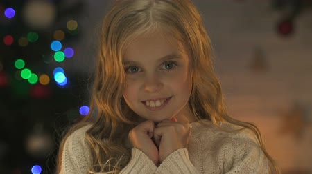 při pohledu na fotoaparát : Happy cute girl smiling at camera, waiting for miracle at Christmas, closeup