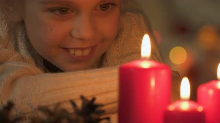 peça : Excited girl looking at burning candles, making wish on Christmas, closeup Vídeos