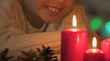 święta : Happy child looking at burning candles, waiting for miracle at Christmas closeup Wideo