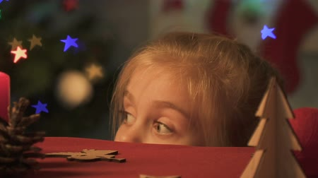 disobedient : Little girl appearing from under table, looking around, doing Christmas pranks Stock Footage