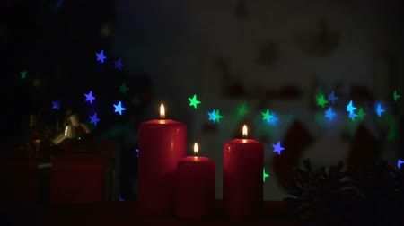 auguri : Candles burning near sparkling Christmas decorations, cozy holiday atmosphere