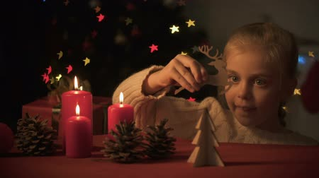auguri : Adorable girl playing with wooden Christmas decorations near burning candles
