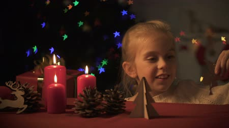 auguri : Adorable girl playing with wooden angel, Christmas tree twinkling, imagination Filmati Stock