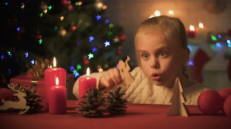 miraculous : Happy smiling girl playing near sparkling X-mas tree, wooden decor for holiday Stock Footage