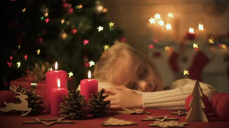 dobranoc : Cute girl fallen asleep on table decorated for Christmas celebration, cozy home