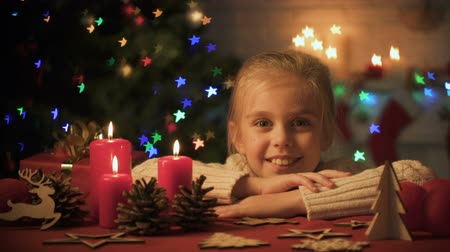 auguri : Little girl looking at Christmas decorations on table, lights twinkling on tree Filmati Stock