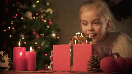 karácsonyi ajándék : Excited girl looking at X-mas present on table with wonderful decorations