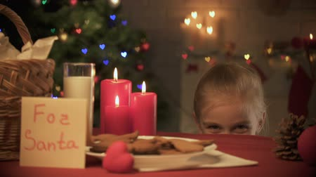 miraculous : Smiling girl looking out under table and taking traditional ginger X-mas cookie Stock Footage