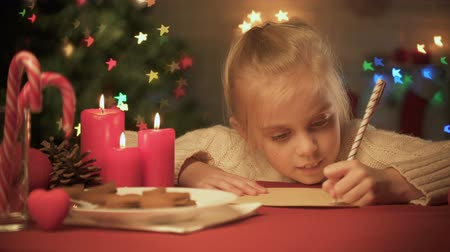 csőd : Smiling girl writing list of presents for friends before holidays, Christmas
